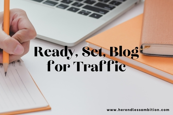 Ready, Set, Blog for Traffic text overlay on image of table with hand writing next to laptop and notebooks.
