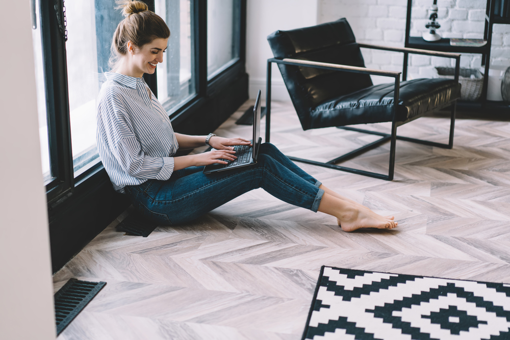 Lady making writer website on laptop while sitting on floor
