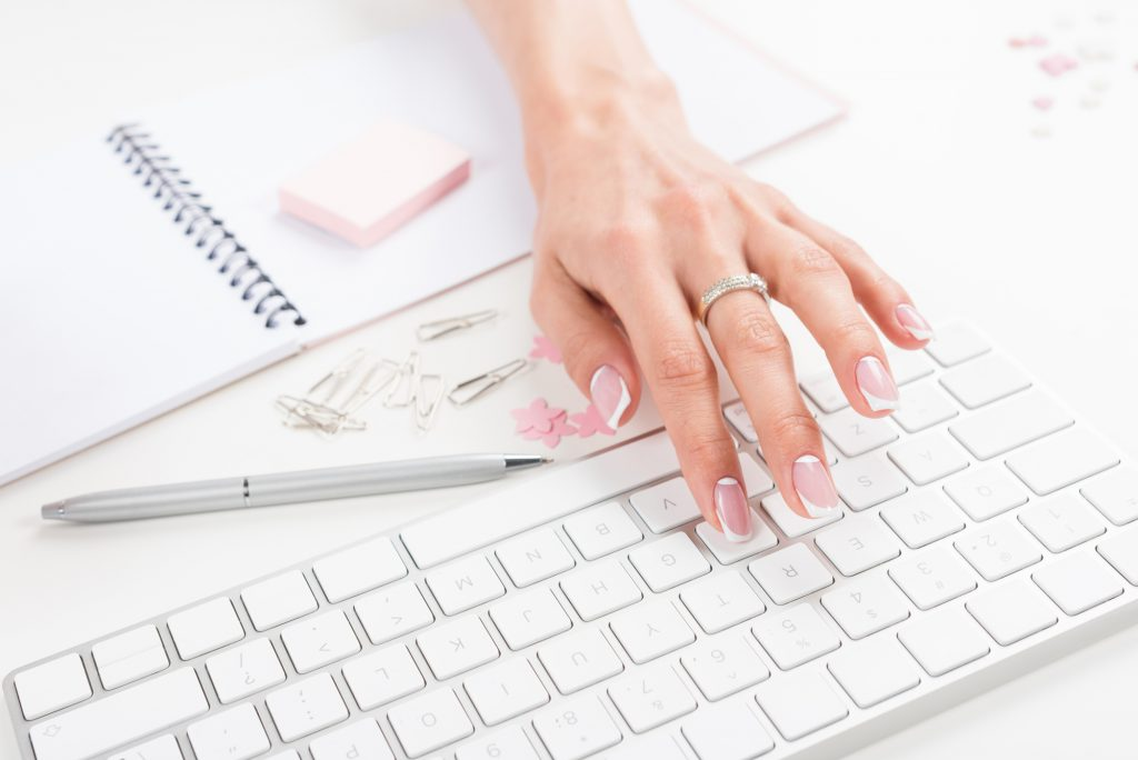 Hands typing on keyboard with items around her on the desk. Ready, Set, Blog for Traffic - Best Low Cost Course for Blog Traffic
